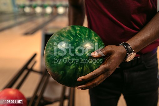 Cheerful friends bowling together, close up on young man hand holding bowl.