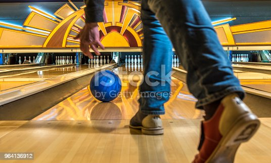 Close-up of a man bowling in a vintage bowling alley