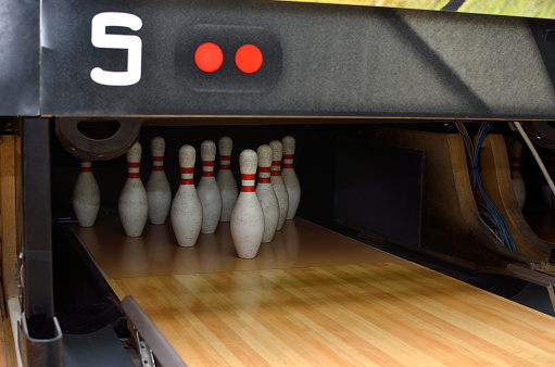 Bowling pins on the alley ready for sport play.