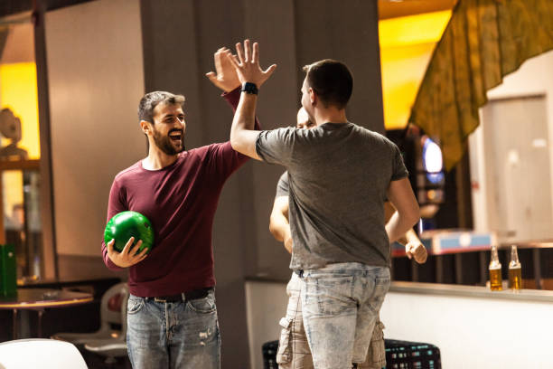 Bowling players celebrating the win Three men are high fiving and celebrating their score in bowling. ten pin bowling stock pictures, royalty-free photos & images