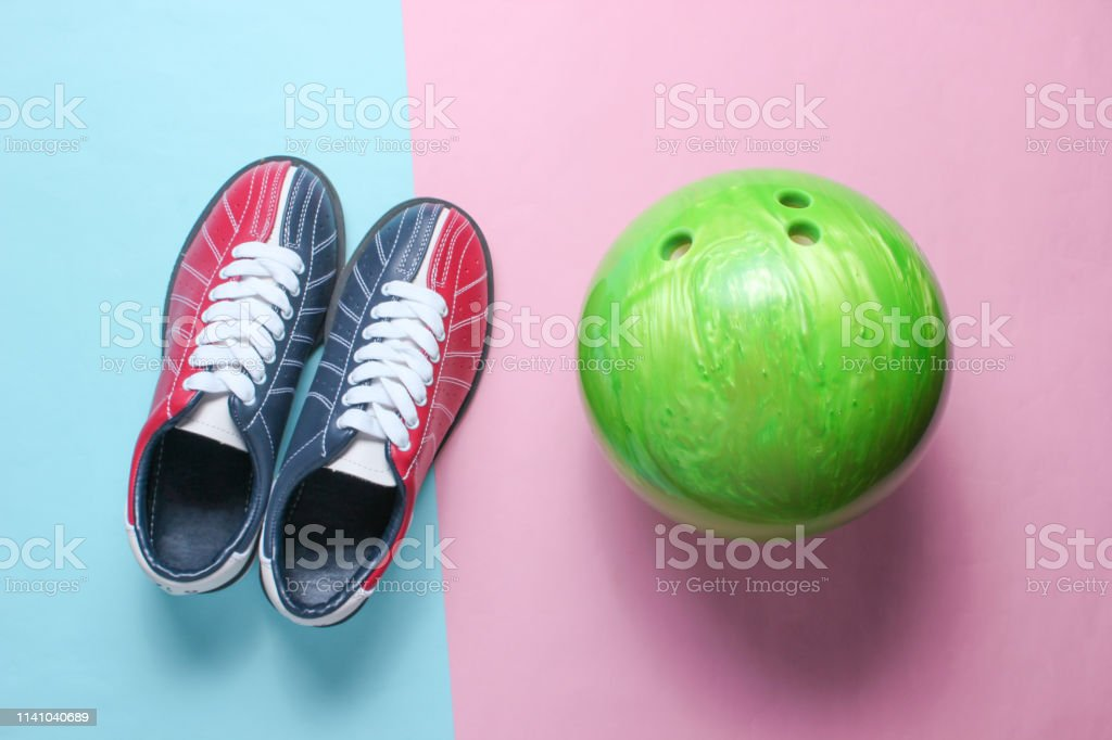 Bowling shoes and bowling ball on a pink-blue pastel background....
