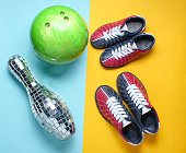 Bowling shoes, disco mirror skittle and bowling ball on blue yellow background. Indoor family sports. Top view. Minimalism