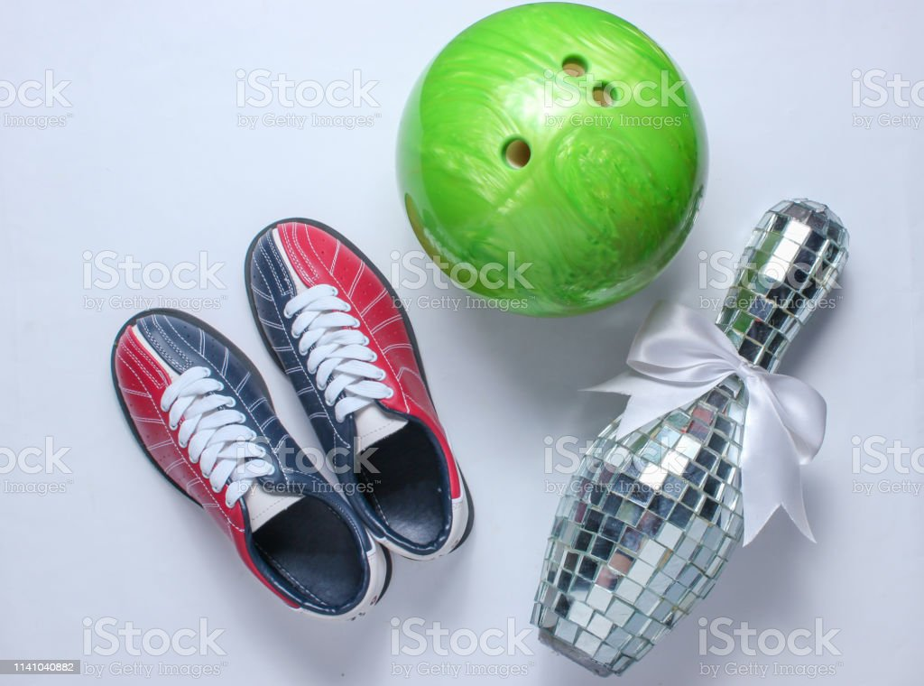 Bowling shoes, disco mirror skittle and bowling ball on white...