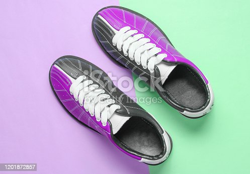 Bowling shoes on purple-blue pastel background. Top view. Minimalism