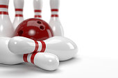 3D graphics of bowling ball and fallen skittles on the playing field (white background). shallow depth of field.