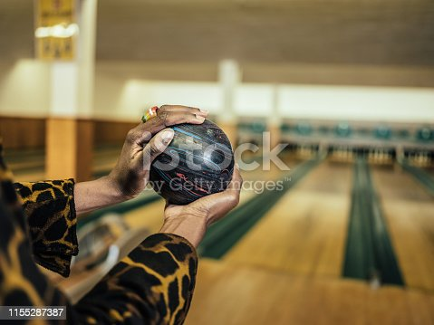 Close up of hands of African millennial woman getting ready to roll the bowling ball, concentrating at the edge of bowling alley.