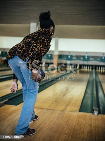 African millennial woman getting ready to roll the bowling ball, concentrating at the edge of bowling alley.