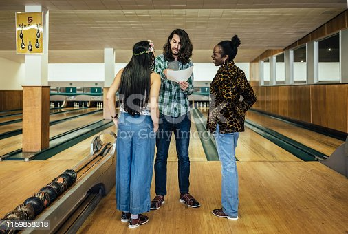 Three millennial friends having fun with bowling, at the bowling alley venue.