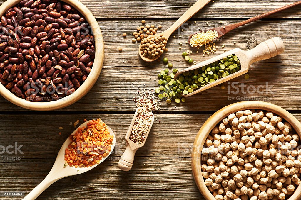 Bowls and spoons of various legumes stock photo