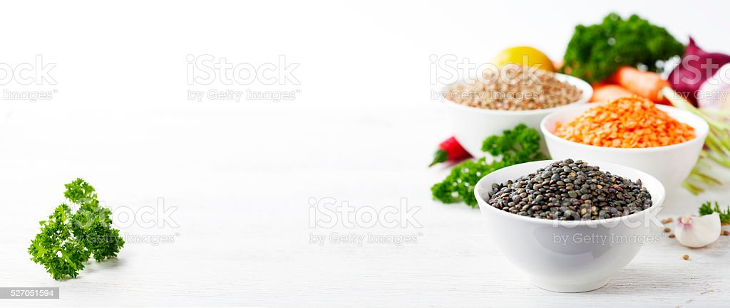 Bowls of assorted dried lentils with vegetables stock photo