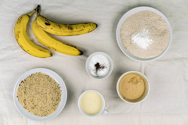 bowls of baking ingredients and ripe bananas - gebackene banane stock-fotos und bilder