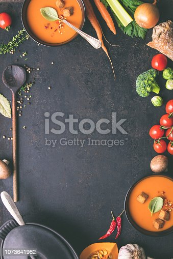Food frame. Bowls of homemade tomato soup and ingredients on rustic background, top view, space for text