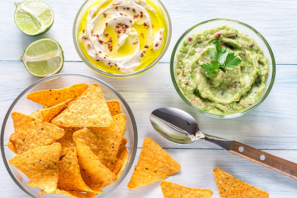 bowls of hummus and guacamole with tortilla chips - koriander hummus stock-fotos und bilder
