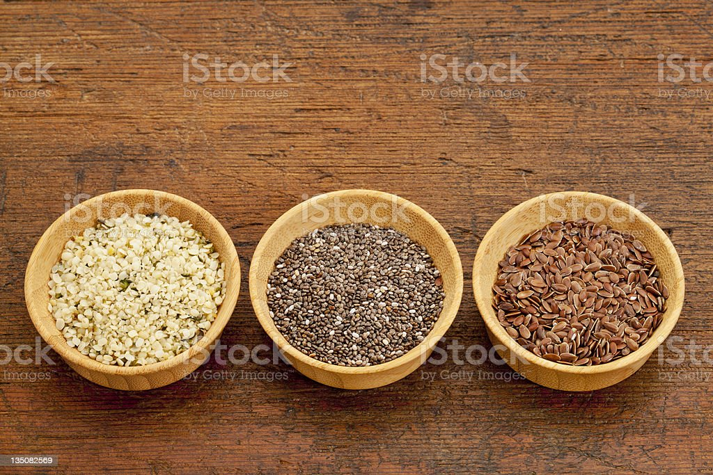3 bowls of seeds, chia, flax & hemp, on rustic wooden table stock photo