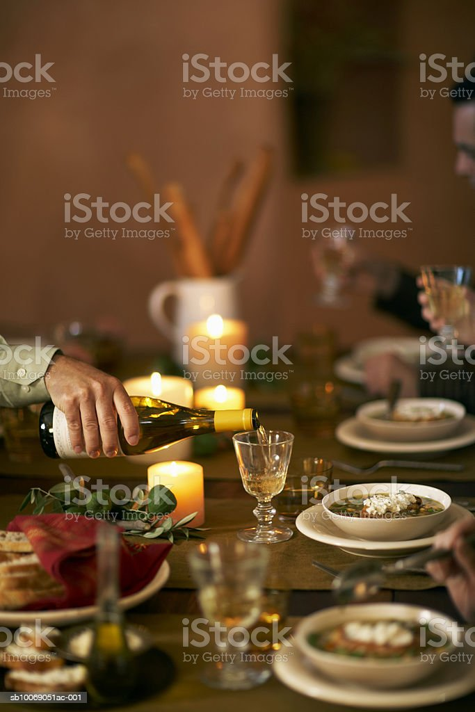 Bowls of soup on dinning table and man pouring wine into glass royalty free stockfoto