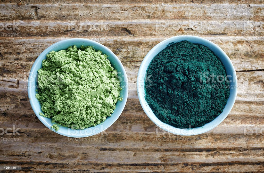 bowls of spirulina algae and wheat sprout powder stock photo
