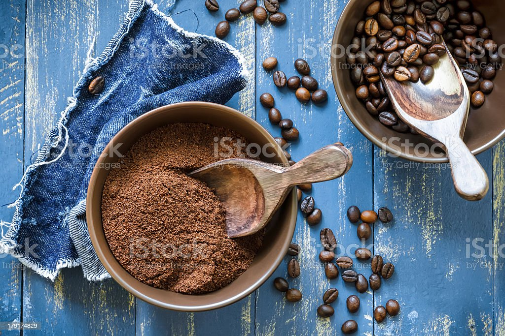Bowls of uncut and ground coffee beans on blue wooden table stock photo