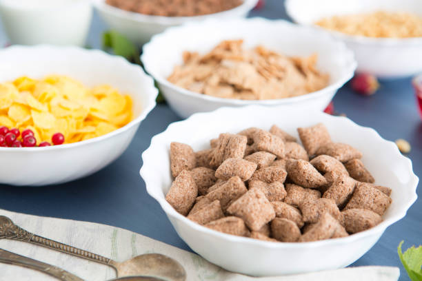 Bowls of various cereals and milk from top view Breakfast cereal mix: cornflakes, pads, muesli, multigrain flakes and chocolate balls stock photo