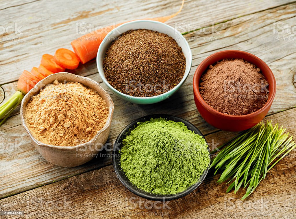 bowls of various dried plant powders stock photo