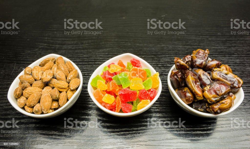 Kekler ve tatlılar eklemeler ile kase: kurutulmuş tarihleri, şekerlenmiş ananas ve kabuklu badem. - Royalty-free Ahşap Stok görsel