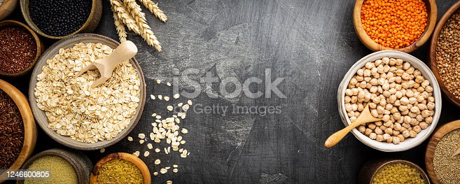 Organic products. Bowls with different gluten free grains on black background, top view