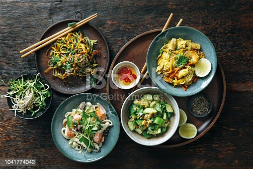 Bowls with Japanese food. Noodles with seafood and vegetables. Udon noodles with salmon. Salad with unagi ell, nori, avocado and tamagoyaki. Salad with cucumbers