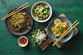 Bowls with Japanese food. Noodles with seafood and vegetables. Salad with unagi ell, nori, avocado and tamagoyaki. Salad with cucumbers