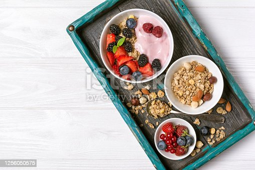 599887760 istock photo Bowls with oat flakes, raspberry, strawberry, blueberry, redcurrant, almond, hazelnut and fruit pink homemade yogurt 1256050575