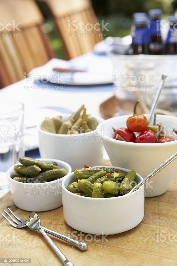 Bowls with pickles, and peppers on table 免版稅 stock photo