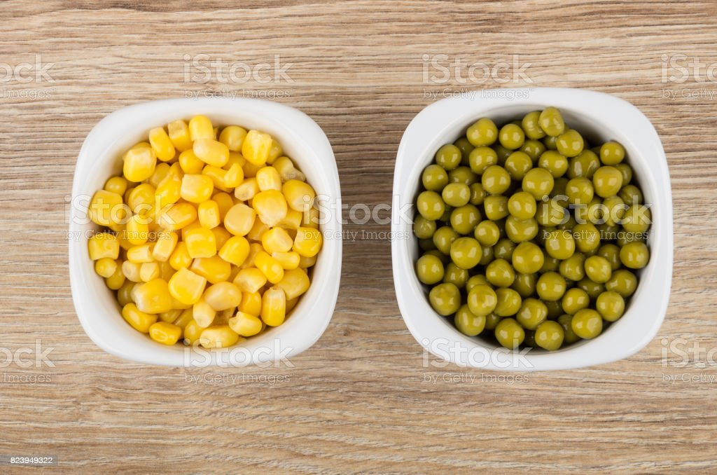 Bowls with sweet corn and green peas on table stock photo