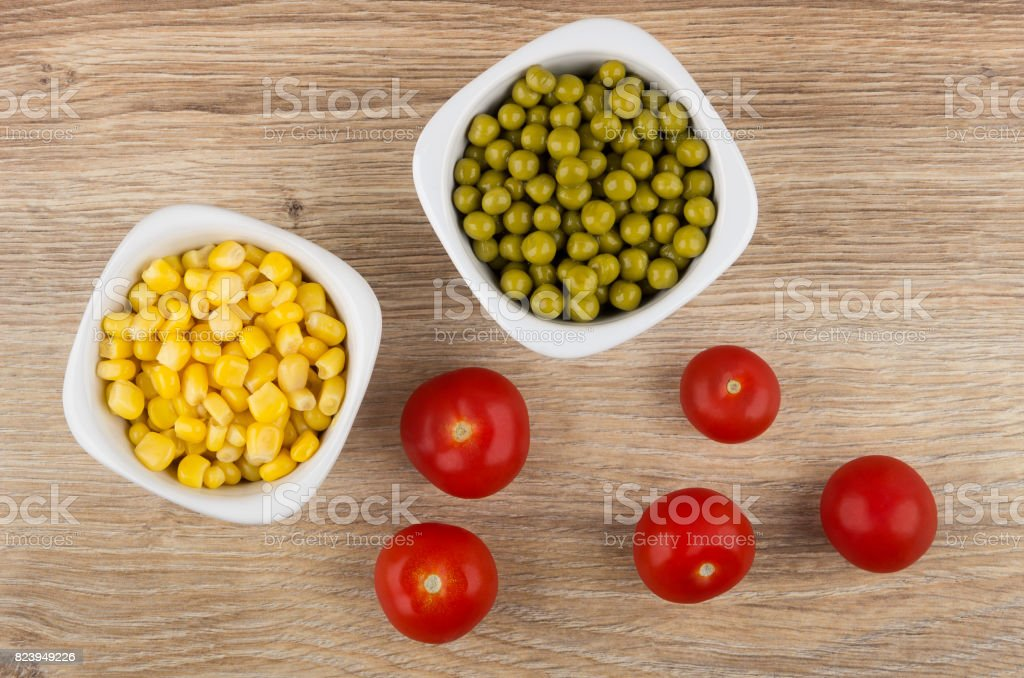 Bowls with sweet corn, green peas and tomato cherry stock photo
