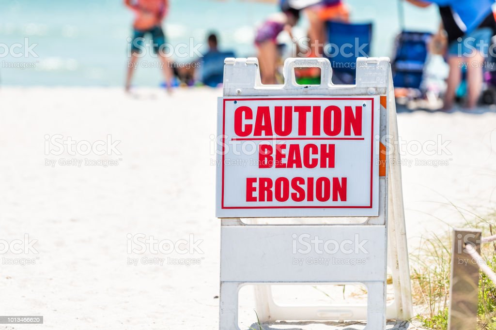 Bowman's beach at Sanibel Island with, many people, crowd in bokeh background, crowded coast, sand, caution erosion red sign closeup danger safety warning royalty-free stock photo