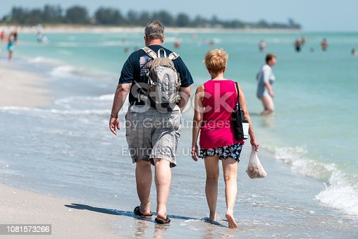 istock Bowman's beach, Florida with colorful turquoise water on sunny day, back of vacation couple walking after shelling with shells, seashells in bag, net 1081573266