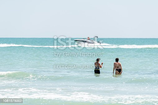 istock Bowman's beach, Florida with one white boat yacht fishing swimming on colorful turquoise water on sunny day, women standing 1081575002