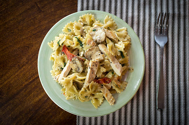 Bowtie Chicken Alfredo Chicken farfalle alfredo with mushrooms and sundried tomatoes bow tie pasta stock pictures, royalty-free photos & images