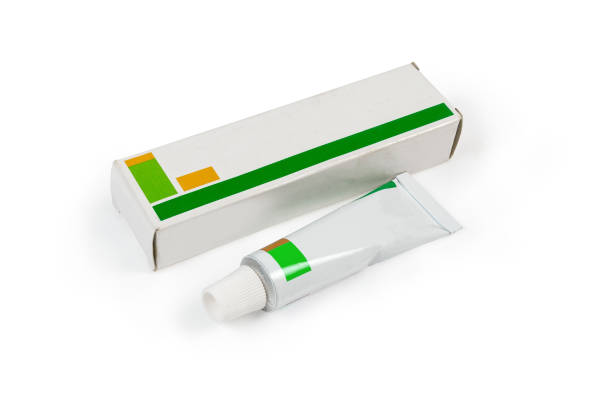 Box and tube with healing ointment on white background stock photo