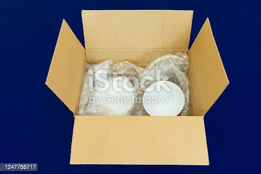 115872043 istock photo Box containing fragile items in protective bubble wrapping 1247755717