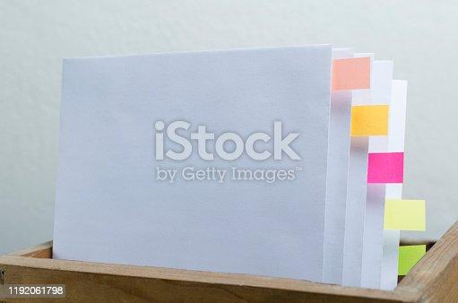 668340340istockphoto Box folder full of documents and bookmarks against white background 1192061798