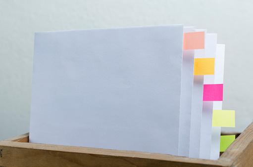 668340340 istock photo Box folder full of documents and bookmarks against white background 1192061798