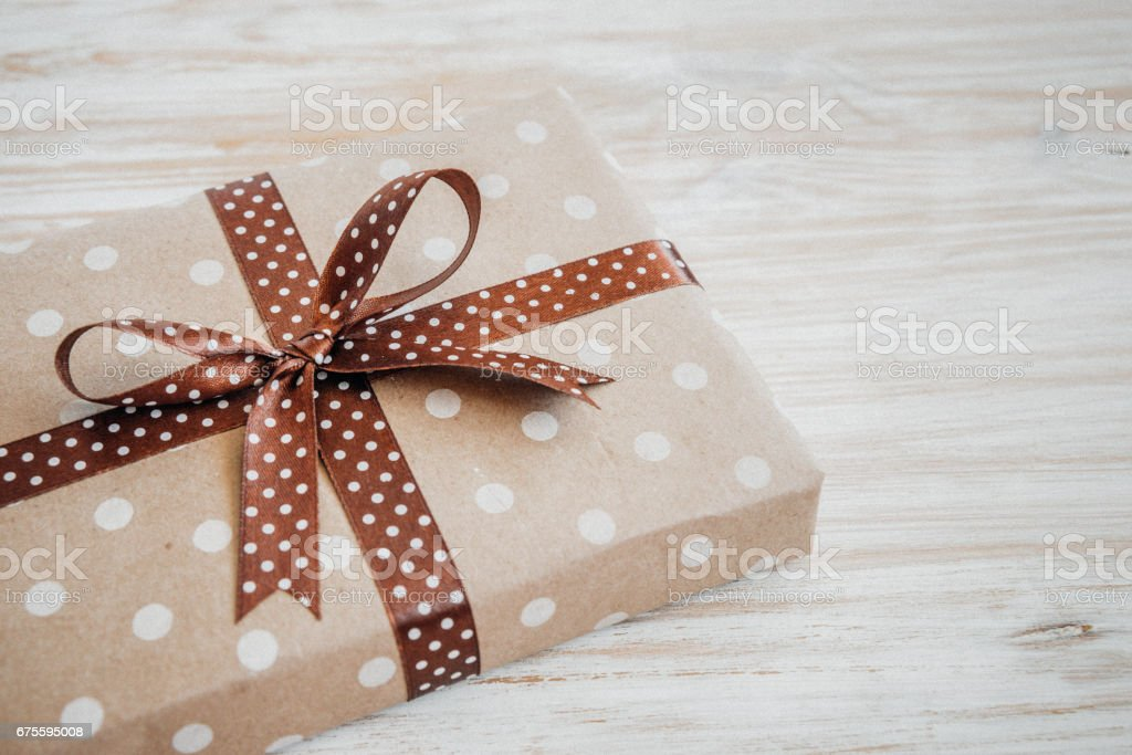 Box in craft paper, eco paper on the wooden table. Top view. Brown paper wrapped gift box with satin ribbon bow on a old rustic wood background. Background for your design. Retro filter photo libre de droits