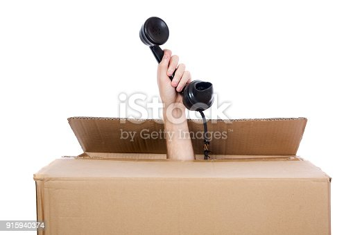 A man's hand sticking out the top of a cardboard box holding a rotary phone receiver. Isolated on white.