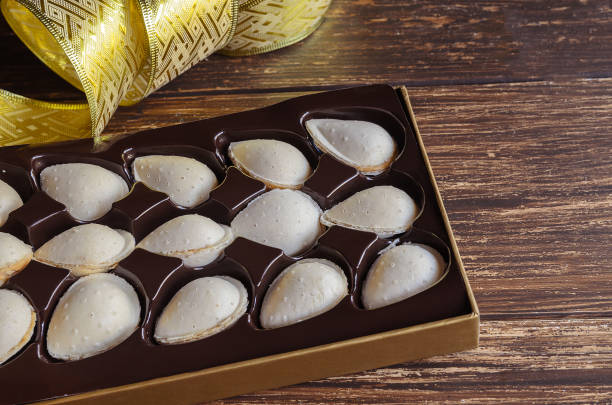 Box of almendras rellenas, almond crisps filled with turron cream. Traditional Spanish Christmas sweets. stock photo