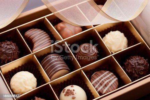 Macro close-up of a gift box of gourmet chocolates with ribbon.