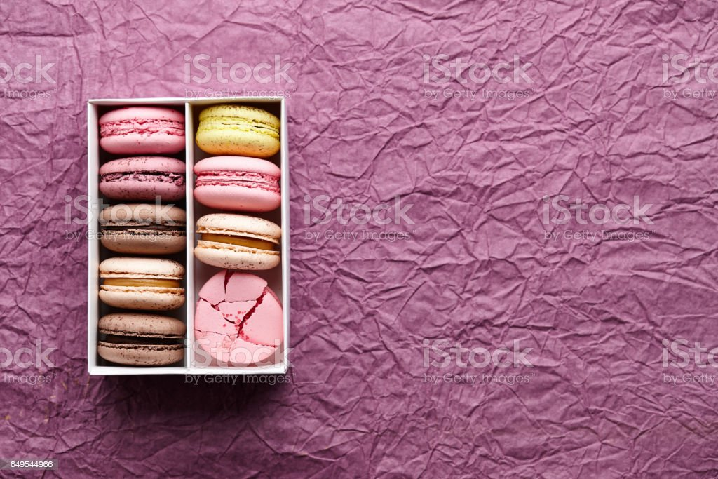 Box of colorful macarons on textured background stock photo