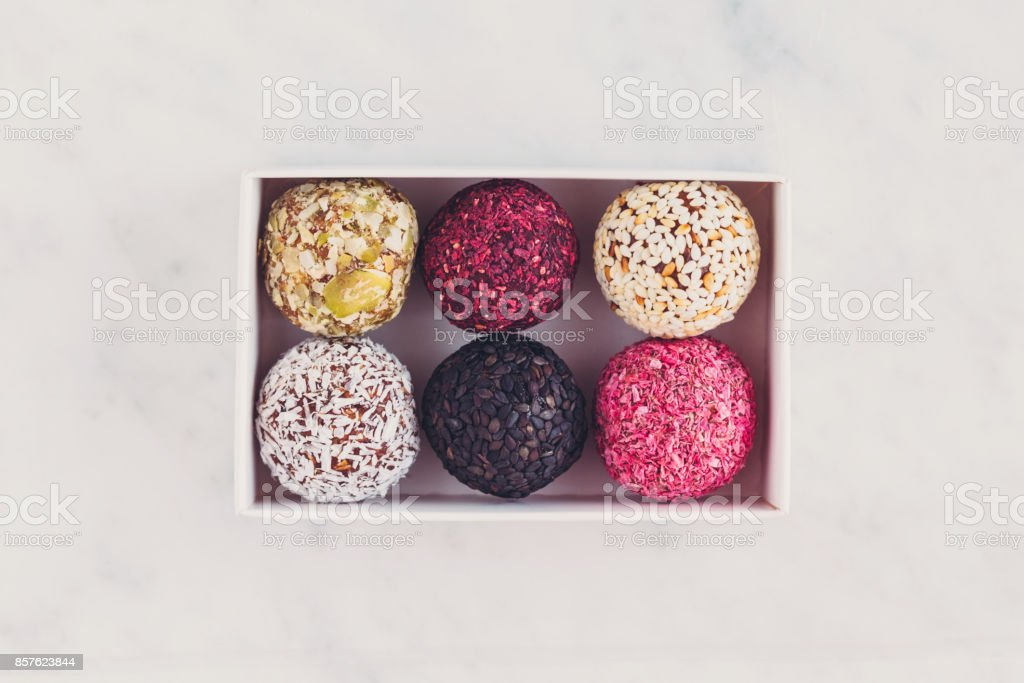 Box of energy raw bites on white marbe table from above stock photo