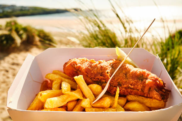box of Fish and Chips at Fistral Beach, Newquay, Cornwall on a sunny June evening. stock photo