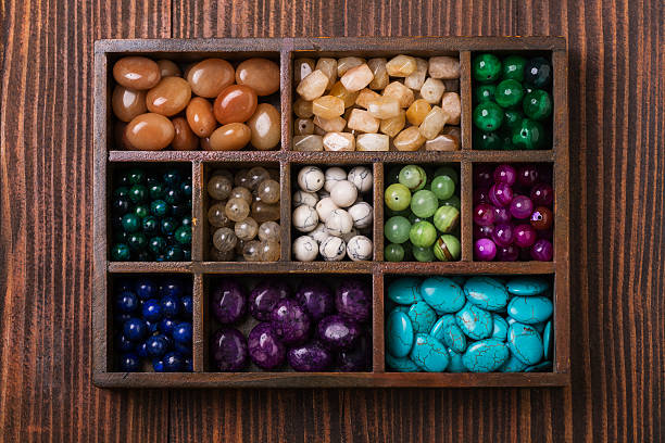 Box of gemstones upper view Box of gemstones on a wooden table crystal healing stock pictures, royalty-free photos & images