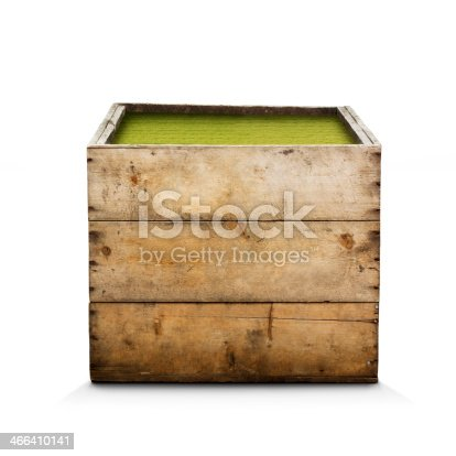 A surreal image worn rustic wooden box, filled with lawn, shot in a studio environment.