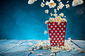 Box of popcorn on blue background, close-up.