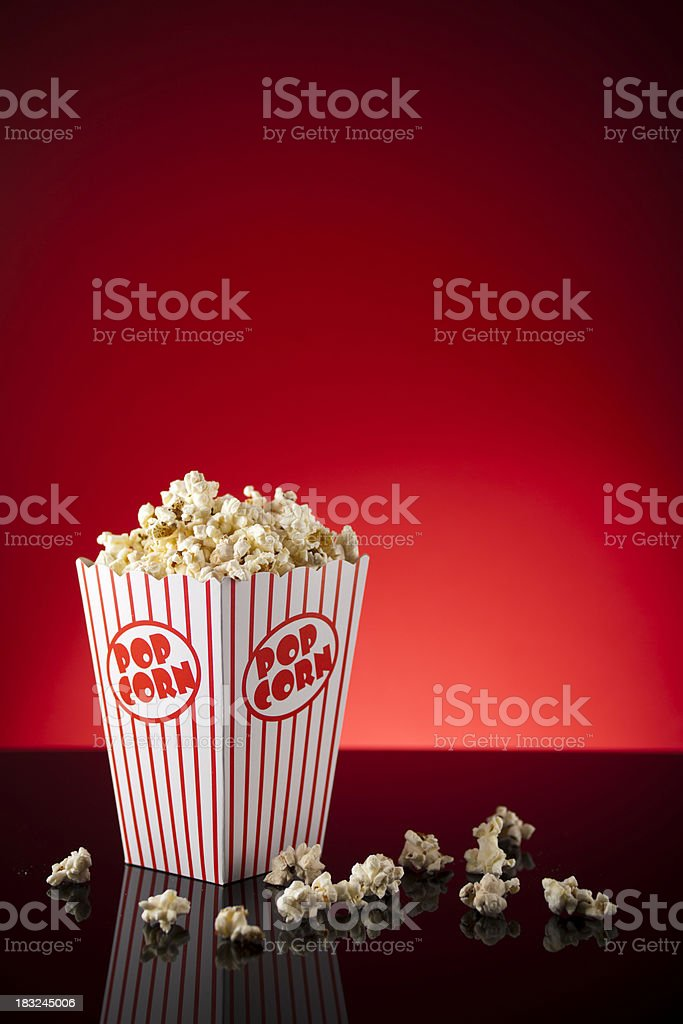 Box of popcorn on reflective surface and red background royalty-free stock photo
